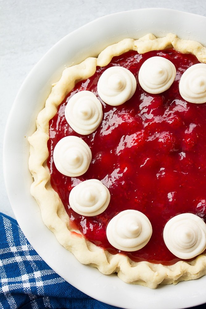 whole vegan strawberry pie, white background, with whip cream.