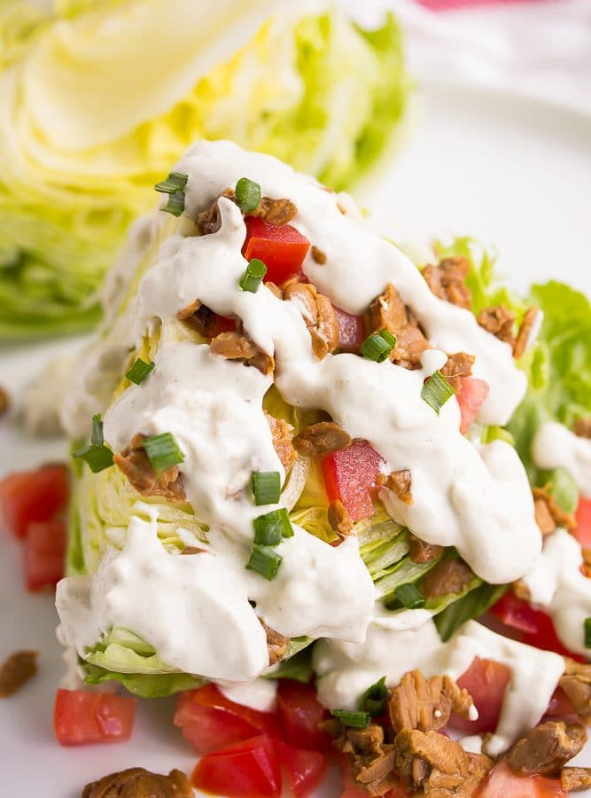 vegan wedge salad with vegan blue cheese dressing drizzled on top.