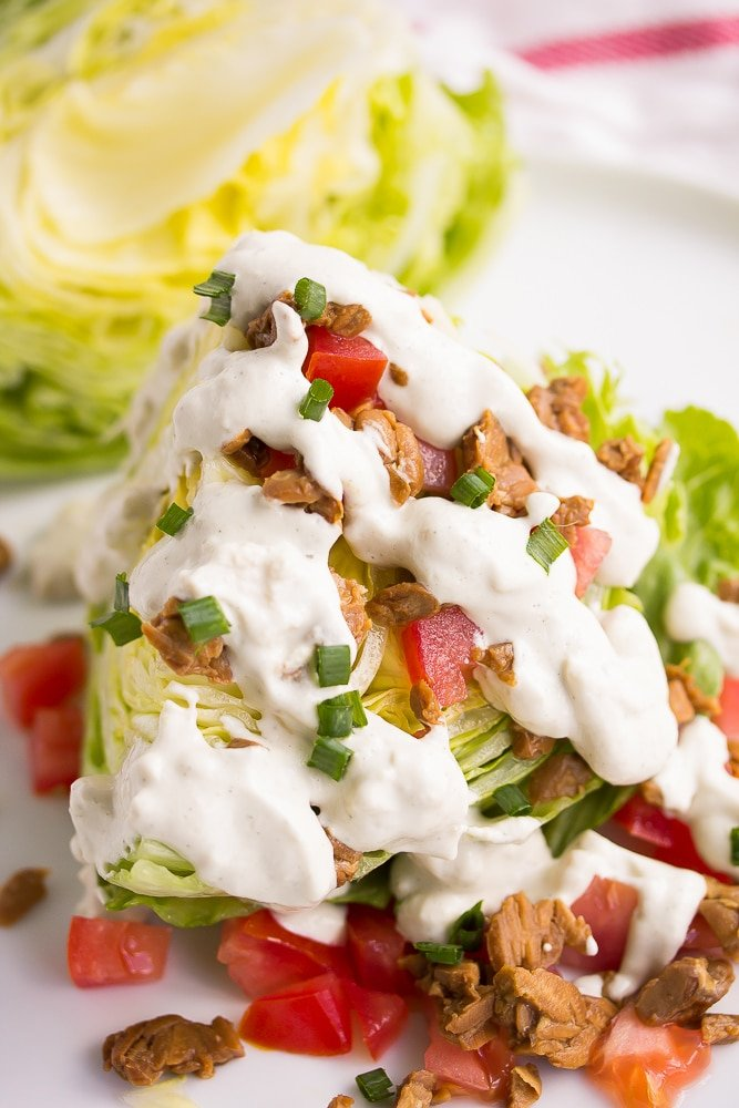 vegan wedge salad with blue cheese dressing drizzled on top.