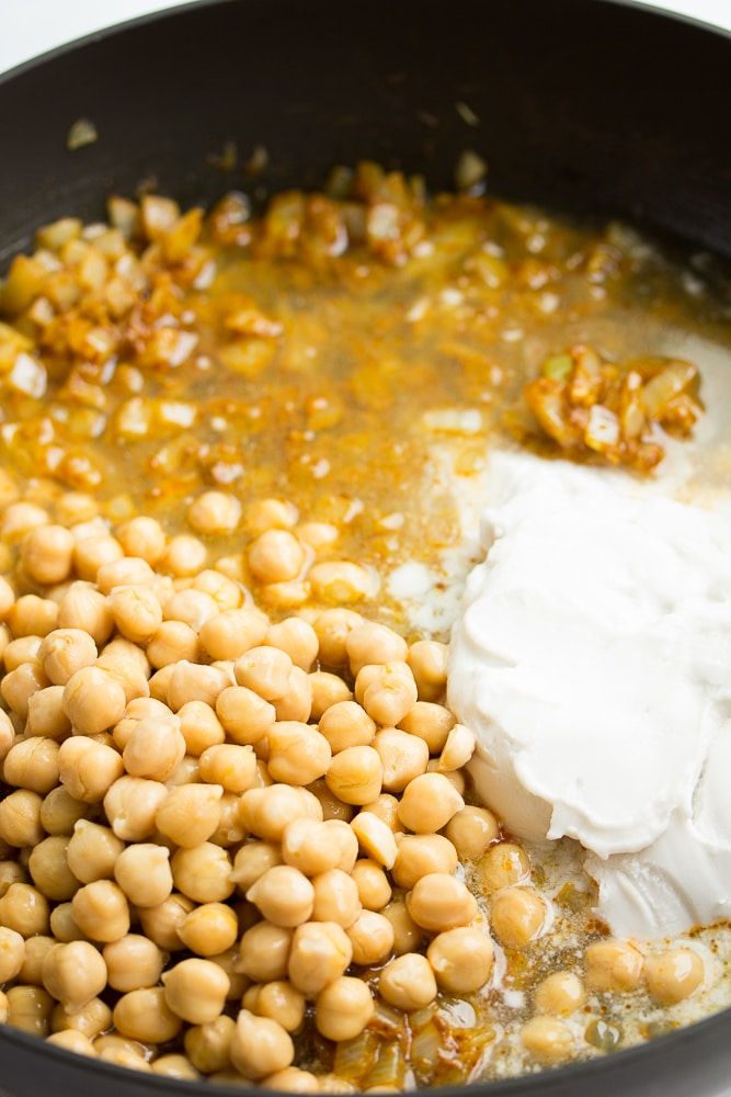 chickpeas, coconut milk added to onions in pan