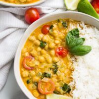 white bowl filled with rice and chickpea curry with tomatoes and basil