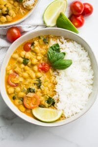 chickpea curry in a white bowl with rice.