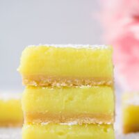 3 stacked vegan lemon bars with pink flowers in background