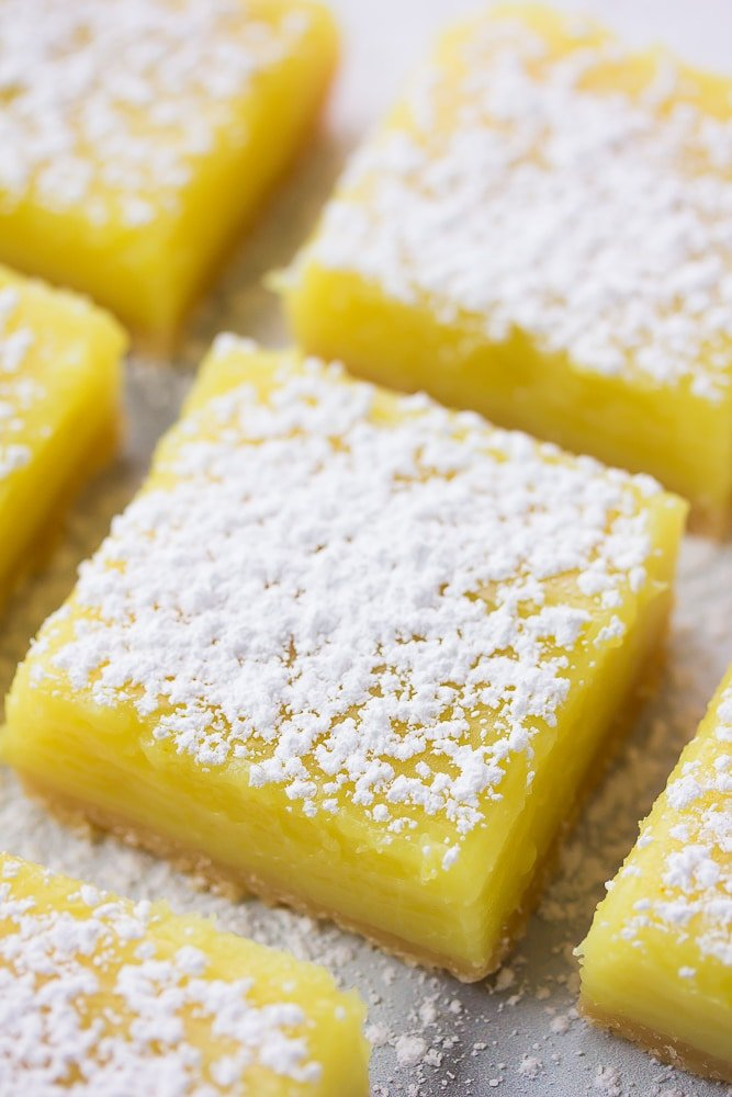 lemon bars with powdered sugar on top all lined up.