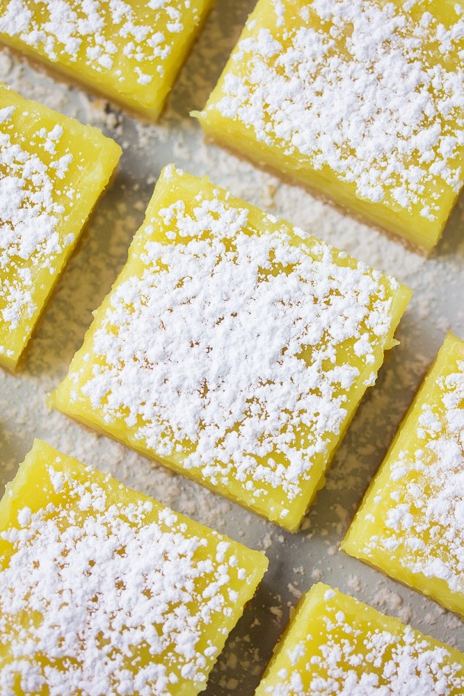 looking down on lined up vegan lemon bars with powdered sugar.