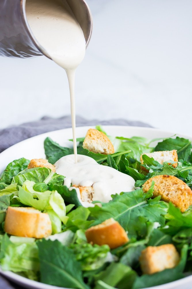white dressing being poured onto a bowl full of lettuce and croutons