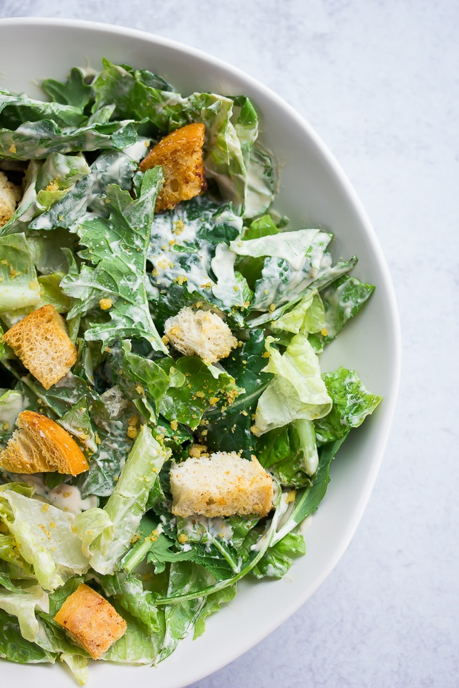 close of up caesar salad in a white bowl