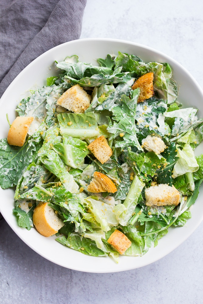 bowl of caesar salad with croutons and white bowl