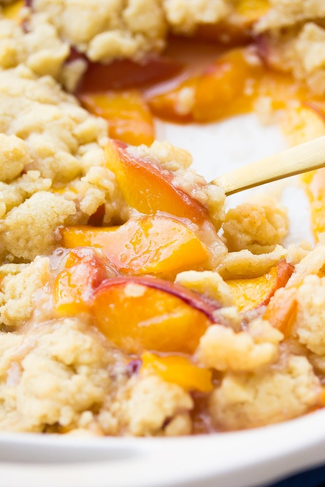 peach cobbler, cooked, with a gold spoon in casserole dish