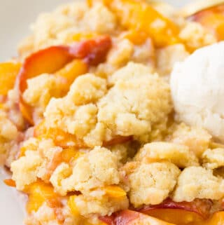 serving of vegan peach casserole in a bowl with soy vanilla ice cream scoop
