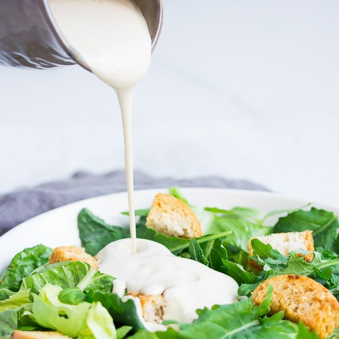 square image of white dressing poured on salad