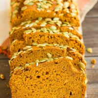 sliced pumpkin loaf with brown wood background and orange towel
