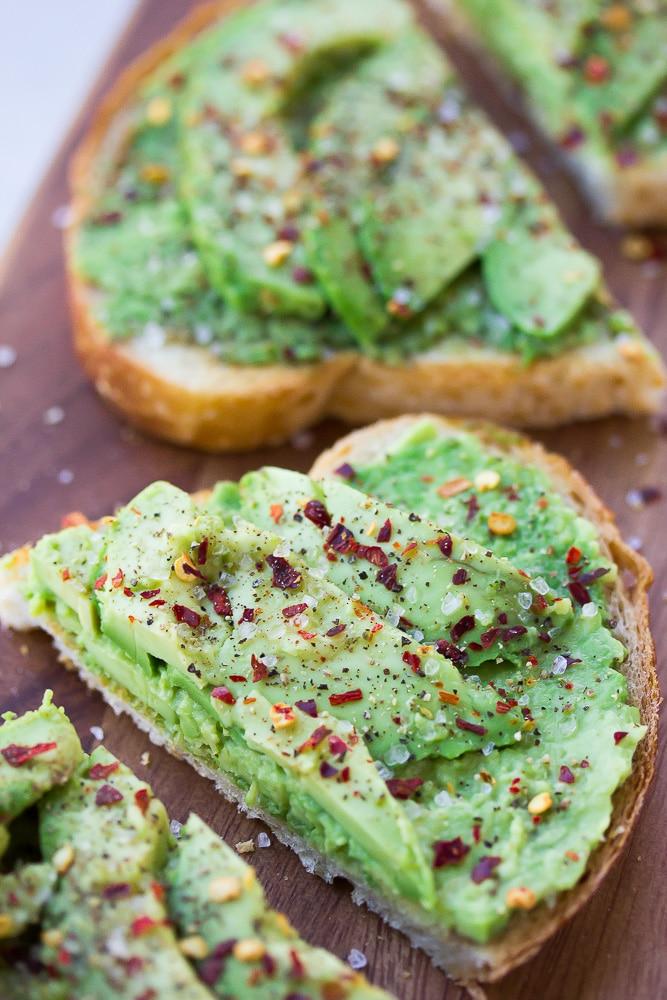 avocado toast cut in half on cutting board