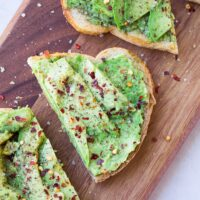 close up of a half of avocado toast sprinkled with red pepper and salt