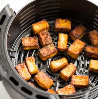 the inside of an air fryer with tofu on it, cooked and crispy