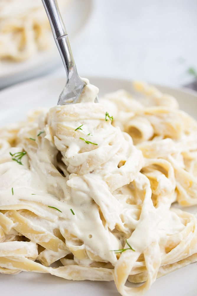 white plate with pasta swirled around a fork