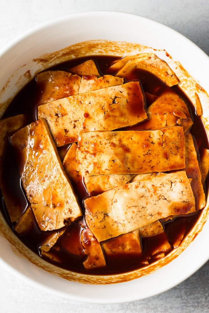 tofu marinating in a white bowl