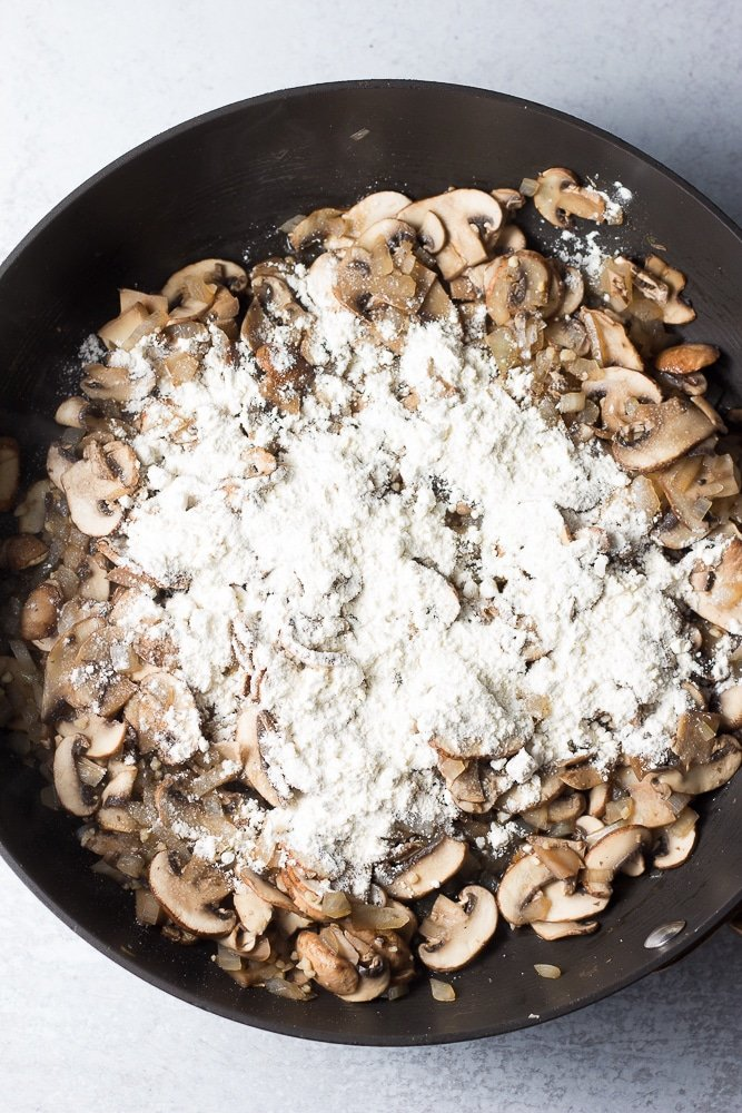 mushrooms cooked in a pan, flour sprinkled on top.