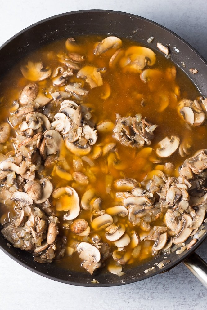 mushrooms cooked in pan with broth added