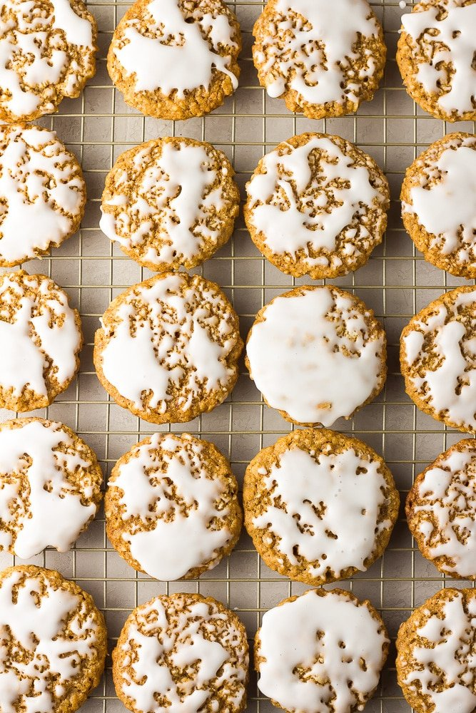 lots of iced vegan oatmeal cookies on a cooling rack