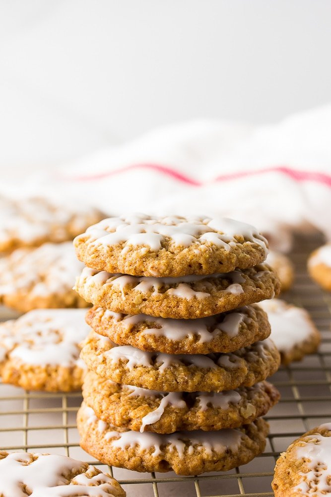 stack of iced vegan oatmeal cookies, red/white towel in background.