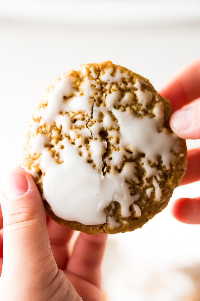 close up of a iced oatmeal cookie with hands pulling it apart.