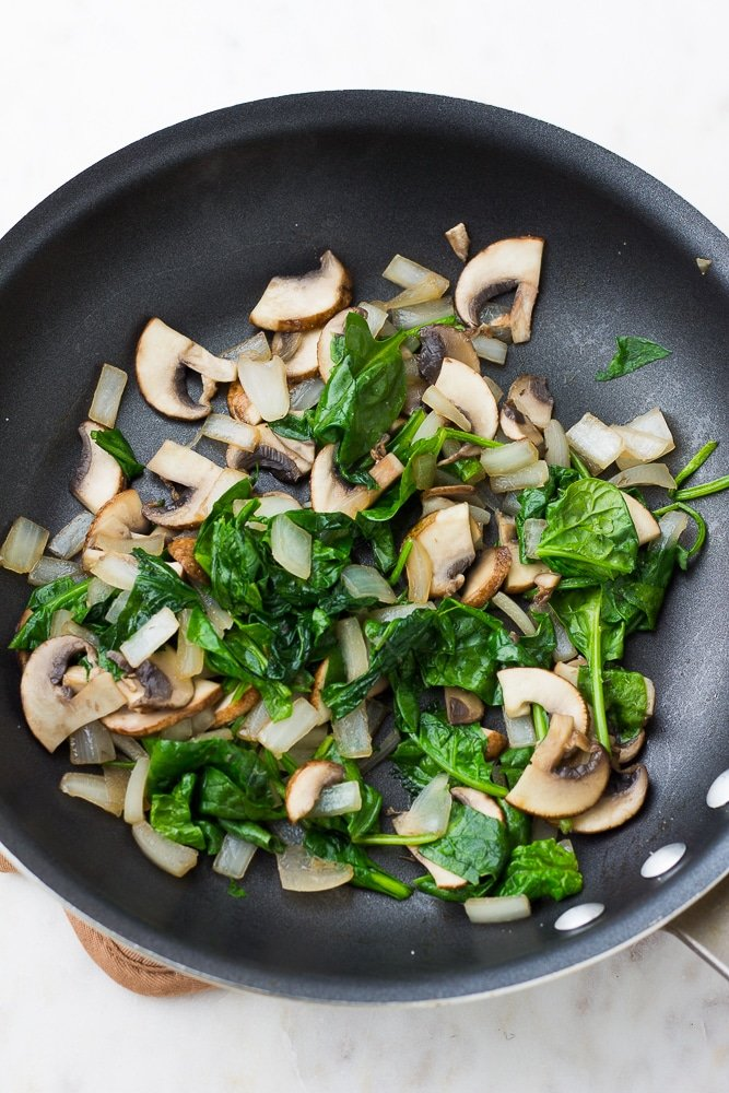 spinach and mushrooms and onions in a black pan being cooked