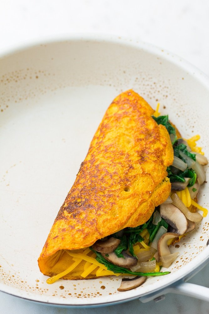 omelette in white pan just flipped and stuffed with veggies