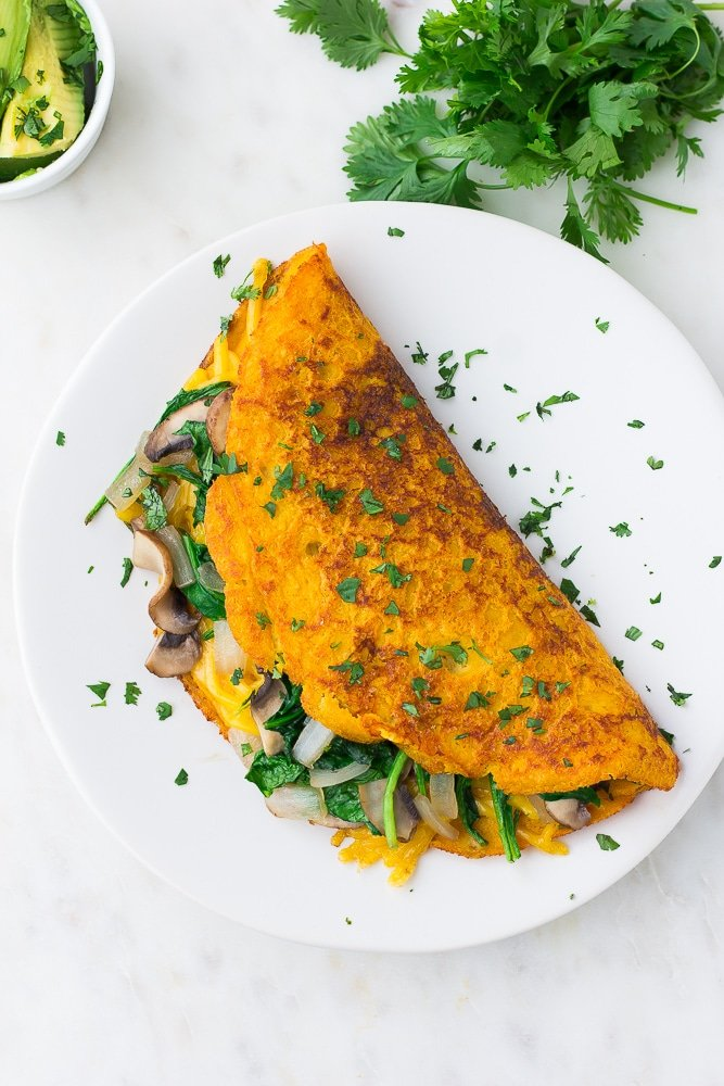 looking down on a vegan omelette on a white plate with cilantro all over it