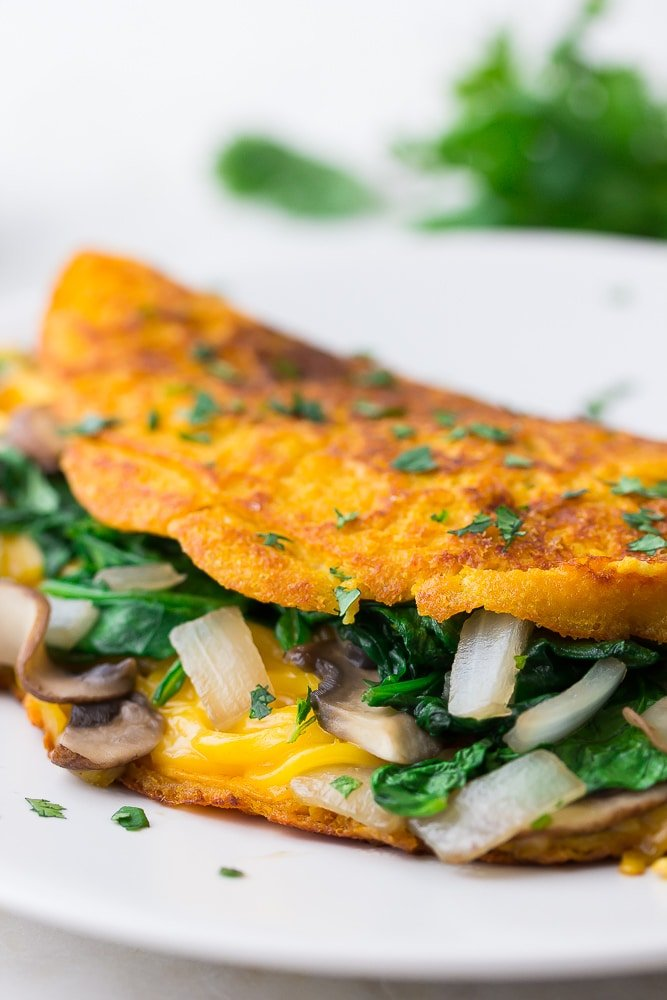 close up of vegan omelette with veggies and cheese inside