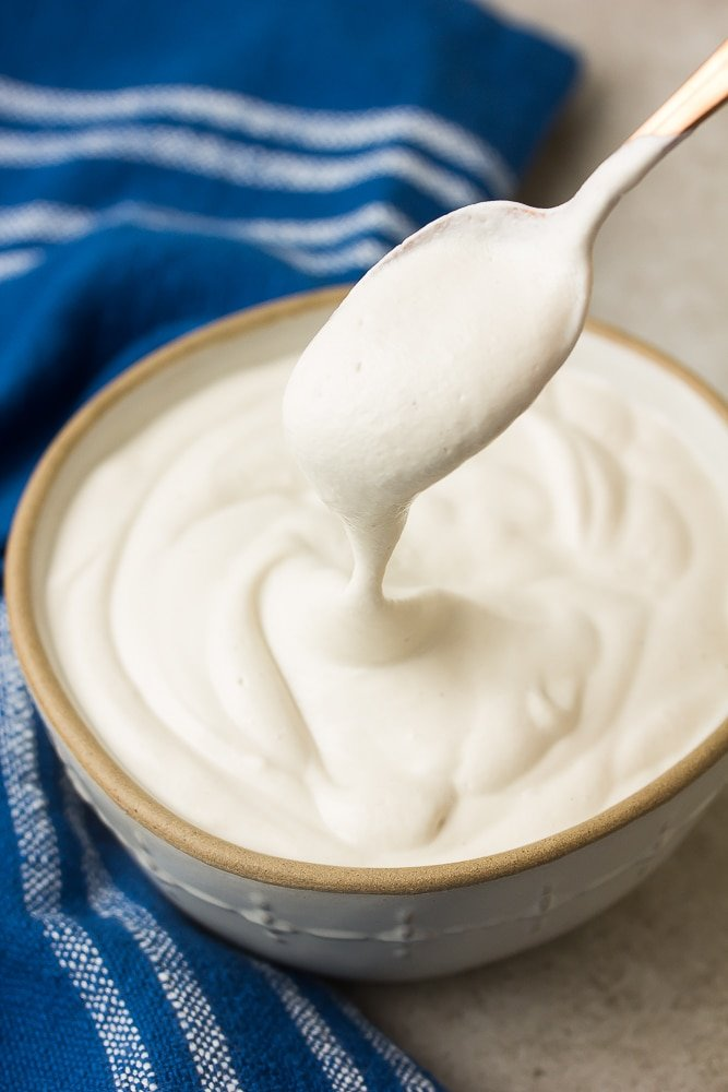spoon lifting out some cashew cream on it from a bowl
