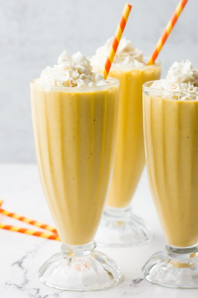 side shot of milkshakes with orange straws and whipped cream