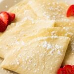 folded vegan crepes on a plate with powdered sugar and strawberries