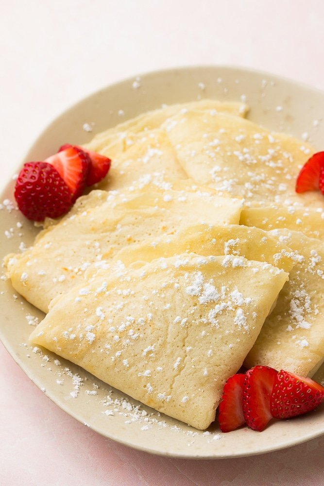 plate of vegan crepes, folded with berries