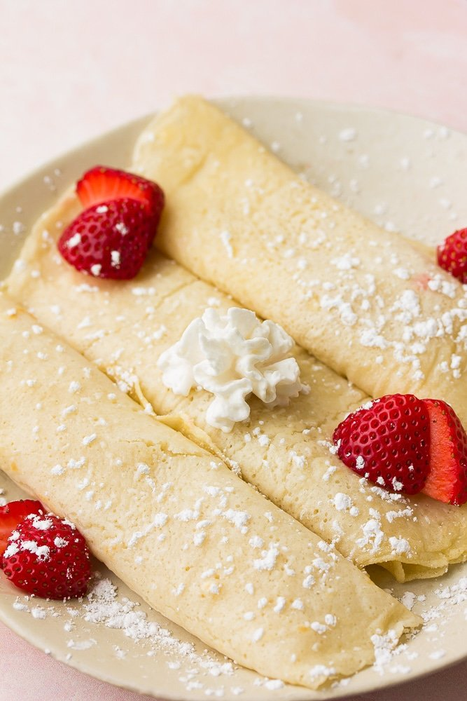 3 rolled crepes with strawberries, whipped cream and powdered sugar