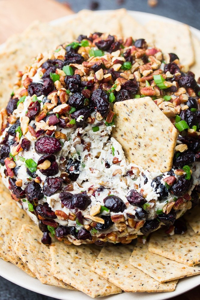 vegan cranberry pecan cheese ball with a cracker in it