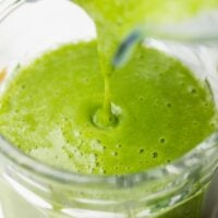 kale smoothie being poured into a cup from blender close up shot