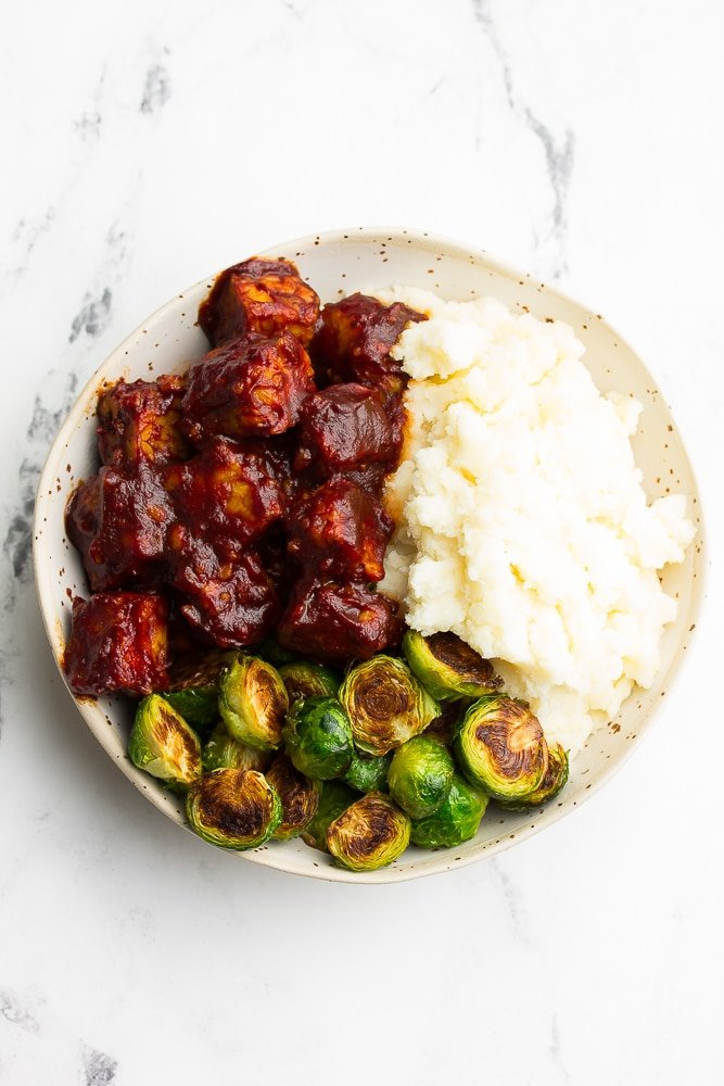white bowl with bbq tempeh, mashed potatoes and brussels, white background