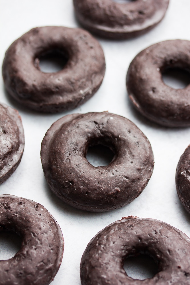 lots of chocolate donuts on grey background
