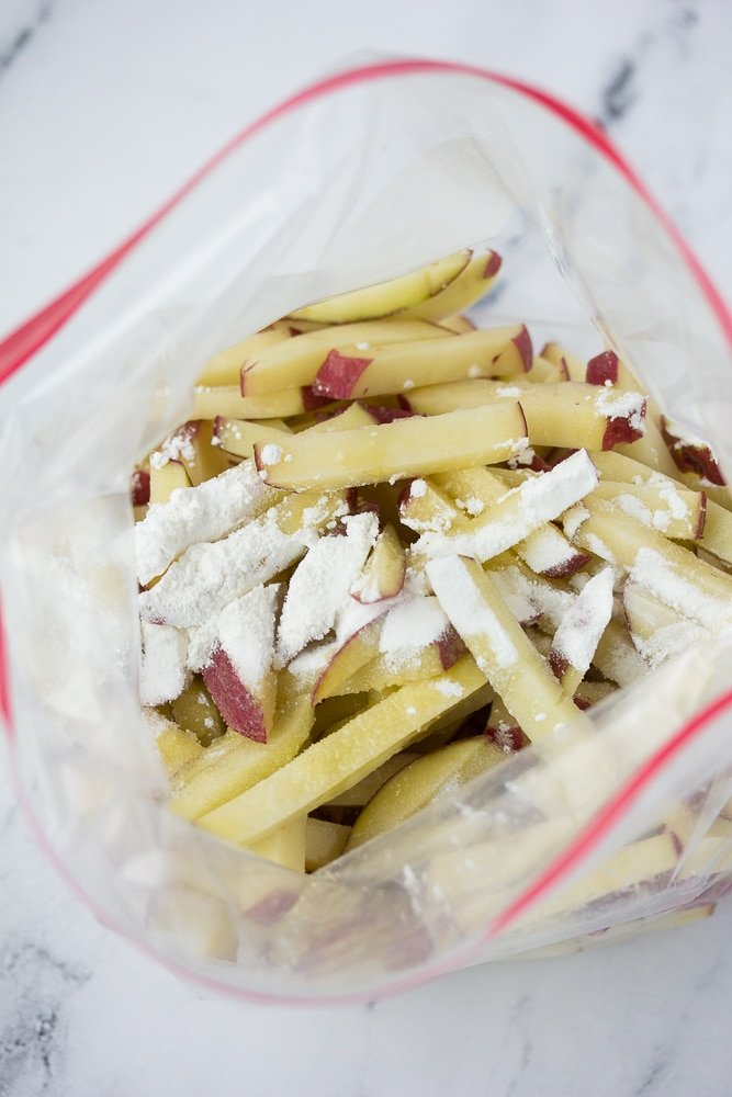 cut potatoes in a plastic bag with cornstarch and oil