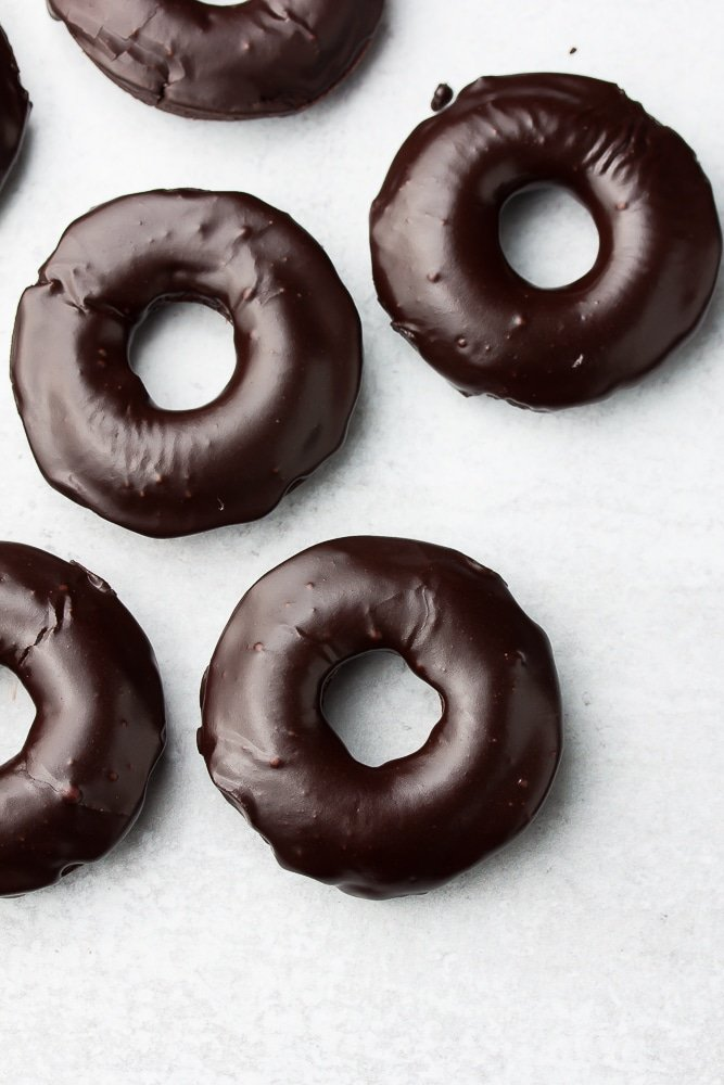looking down on several chocolate donuts on grey background