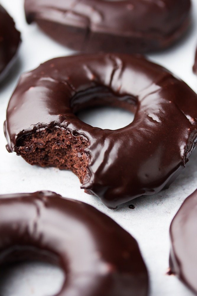 close up of a chocolate donut with glaze, a bite taken out of it
