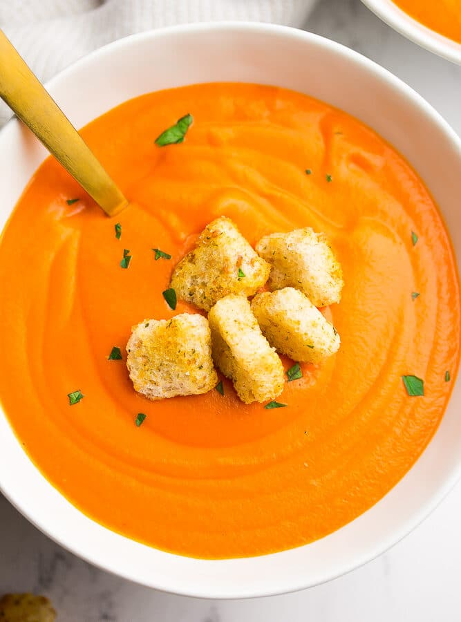 bowl of tomato soup with croutons and a gold spoon in it