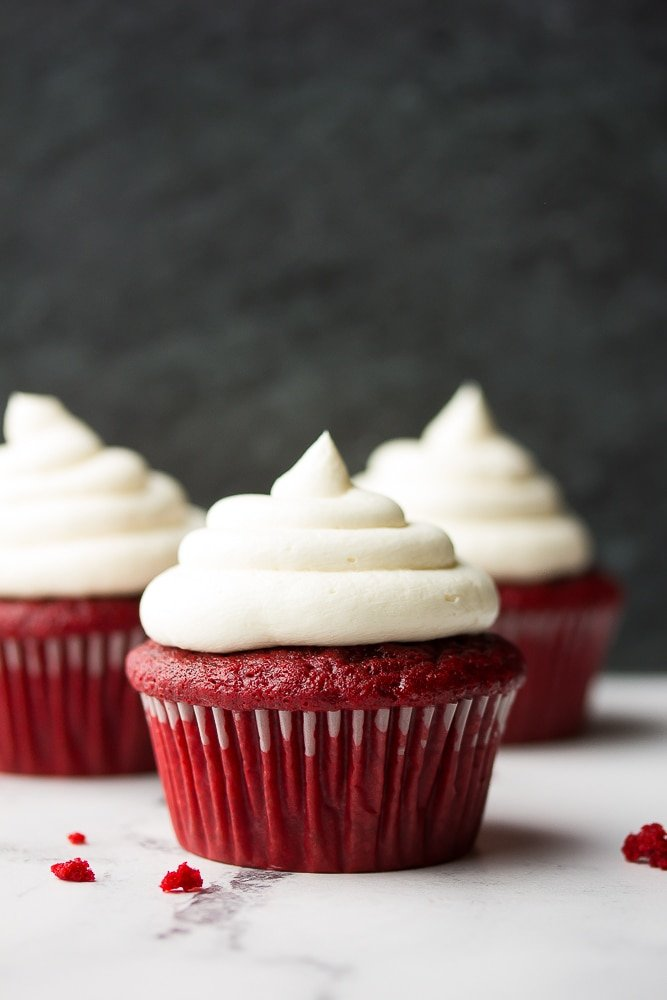 3 red velvet cupcakes with black background