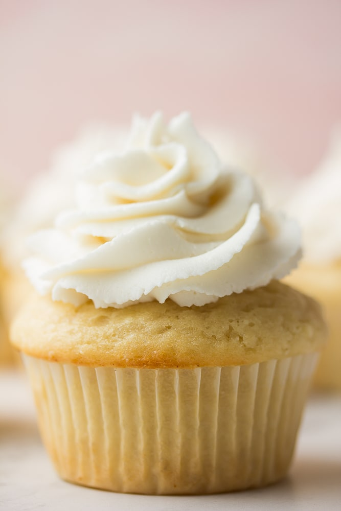 close up of a vegan vanilla cupcake, pink background