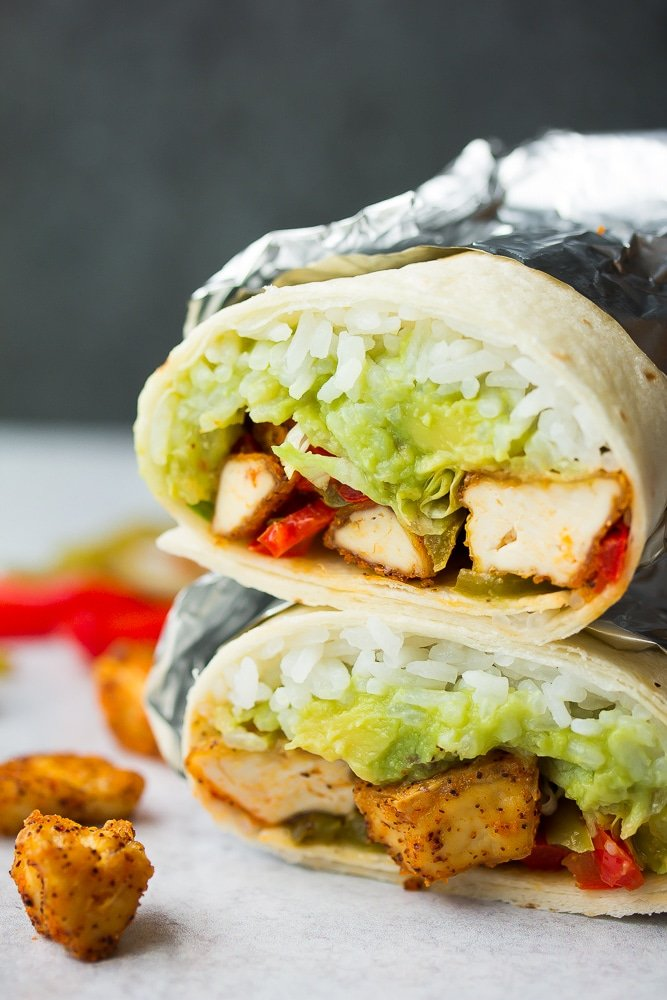 burrito with what looks like chicken, peppers, guac and rice