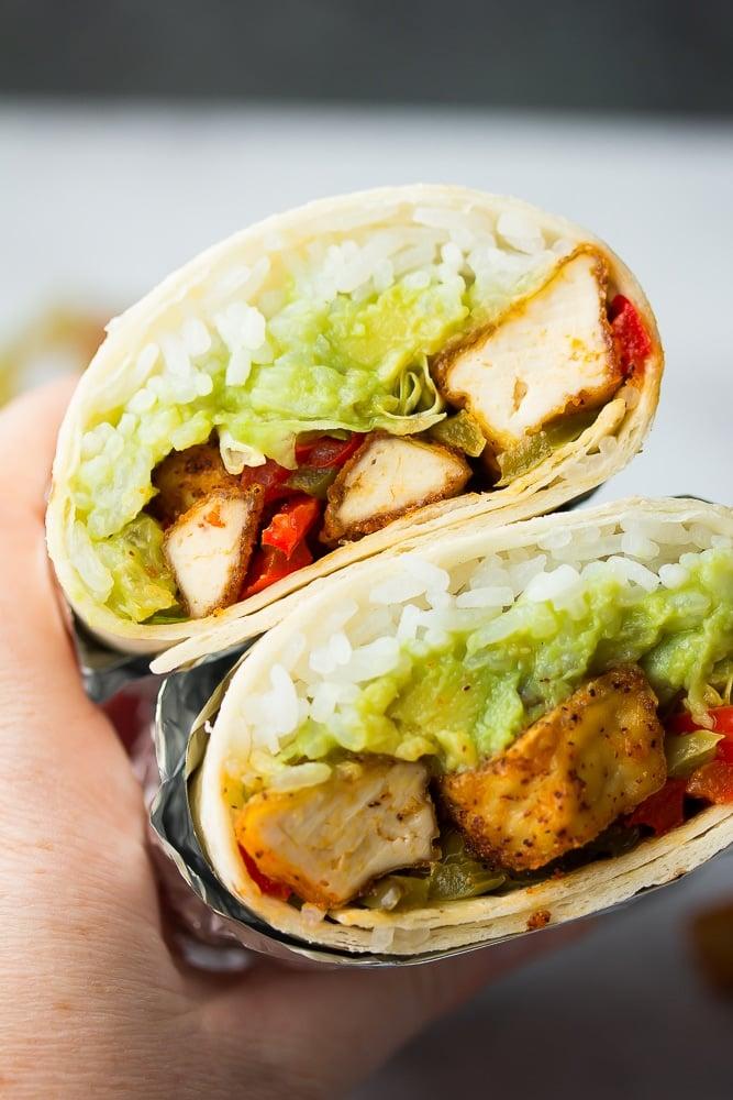 burrito with vegan chikn, lettuce, guac, black background