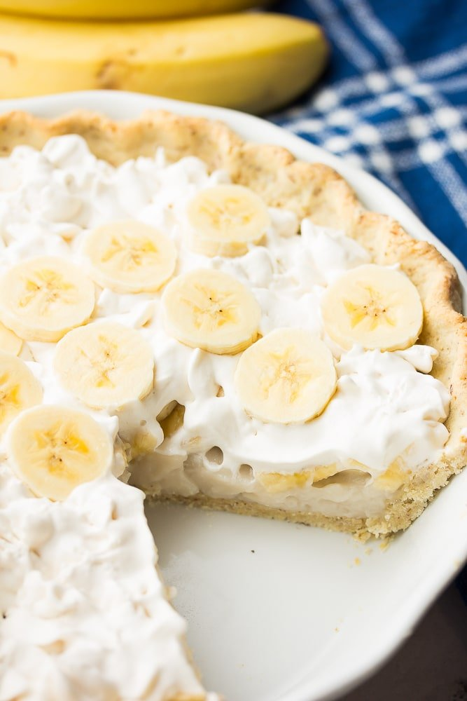 piece of banana cream pie cut out, bananas in back