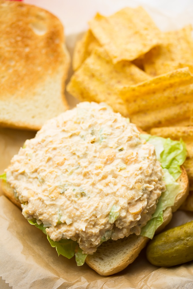 tuna spread on a piece of bread with chips in background