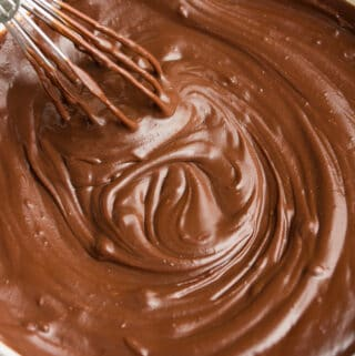 square image of bowl of chocolate ganache with whisk